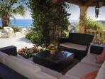 Covered outside sitting area with pool and sea view