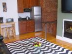 Furnished kitchenette with stainless refrigerator and granite bar.