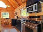 The kitchen opens to the dining area and has a high end 6 burner Frigidaire range and oven, microwave, and all the...