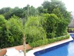 View from Bedroom 2 of the large pool backed by the Playacar Aviary