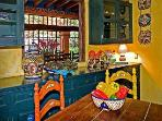 Colorful kitchen with view of dining room and garden
