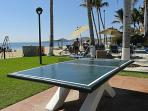 Table tennis poolside.