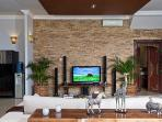 View of sofa, Tv, kitchen on the left, and Balinese doors to the guest toilet on the right.