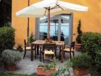 Stone patio and garden with teak table and chairs for casual dining and spectacular views