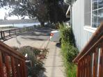 Big, long yard with basketball hoop right outside of the house over looking the bay