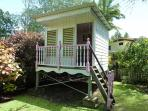 Cubby house complete with table & chairs and a variety of toys, swingset
