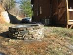 Outdoor stone fire pit with built in seating around it - great for roasting marshmallows.