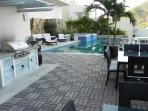 Teak Wood Party Deck with Gas BBQ Grill next to the shared Pool for Entertaining Guests