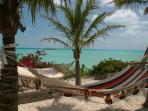 sandy area with hammocks in rear of villa