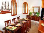 The dining area, just off of the kitchen and island, is a formal and sheltered setting for meals.
