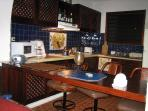 Sitting at the bar, enjoy the spacious kitchen done in blue Talavera tile decor.