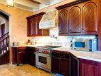 You'll love cooking on the Wolf range & elegant custom mahogany cabinets.