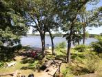 Looking from the deck, the backyard has grassy area, fire circle, boat dock and sandy beach