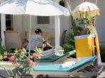 Our friendly in-house spa staff setting up a lounger for a relaxing massage by the pool.