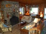 A large fieldstone fireplace anchors the living room with views of the lake