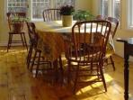The sunny dining room seats 6 people and overlooks the perennial garden and heated pool