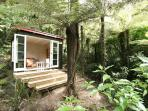 'Summer house' nestled in the rain-forest across the stream ...