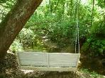 Follow the trail behind the Dream Chalet to a Bench Swing suspended from a tree overlooking a creek