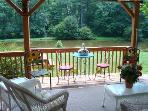 Covered Deck with Love Seat & Chairs Overlooks Extensive Lawns and Pond