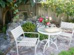 Cozy, romantic table in back garden area. Help yourselves to yummy edible loquats when in season.