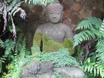 Buddha in waterfall niche at pool