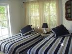 2CD BEDROOM WITH TV AND  2 TWIN BEDS FRENCH DOORS OPEN UP TO DECK WITH TABLES AND CHAIRS WITH LIBRARY AND TV