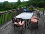 The deck features a dining table, chairs and a gas grill.hairs.
