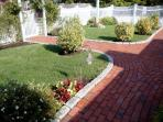 Bricked walk surrounded by flower beds leads from driveway to front porch.
