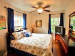 Master bedroom has a comfy king sized bed, ceiling fan and TV