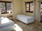 Bedroom #4 with garden views and balcony...configured as a queen or double beds.