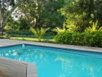 The pool is close to the covered patio with full barbeque facilities and direct access to the garden with large trees...