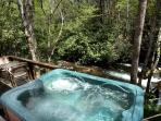 Hot tub on deck next to waterfall
