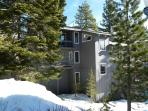 Side view shows master suite's 3rd floor private balcony deck and 2nd floor entry. Winter.