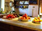 Fruit & vegetables on the marble-topped Island in the kitchen. Plenty of tea pots for Brits.