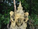 Balinese statues and Indonesian stonework are dotted around the tropical garden