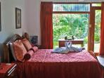 Mini-Master 1 Suite with Queen Sized hand carved bed overlooks manicured gardens and Rainforest