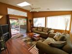Large screen TV and overstuffed couches open to patio