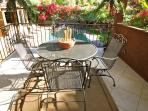Sun-dappled dining area surrounded by lush desert flowers