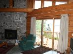 Sliding patio doors flank either side of the floor to ceiling field stone fire place.