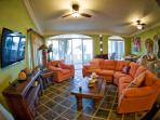 Main floor living room with adjoining deck has spectacular sunset and ocean views