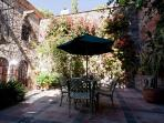 Cactus garden, table and chairs, under parsol, arched windows, master bedroom suite on second