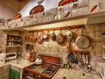 Kitchen, gas stove, copper pots and and pans, ornamental plates, pineapple motif chimney