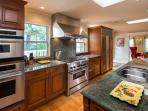 Gorgeous kitchen with hardwood flooring, and doors off patio for outdoor  BBQ.