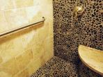 Oversized river rock shower with chlorine filter, seat and grab bar.  Ideal for the elderly.