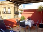 The terrace is furnished with sun-loungers, table and chairs.