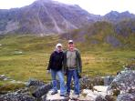 Hosts Kevin & Geri McCann enjoying hiking in Hatchers Pass surrounded by jagged peaks