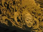 Elaborate stone carving, carved in place over the entry door.