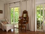 Master Bedroom lounge chair and antique dressing tablewith view to outdoor verandah and jungle gorge