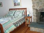 Downstairs bedroom with queen bed and fieldstone fireplace