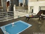 Hot tub and lounge chair overlooking the city. Partial river view.
